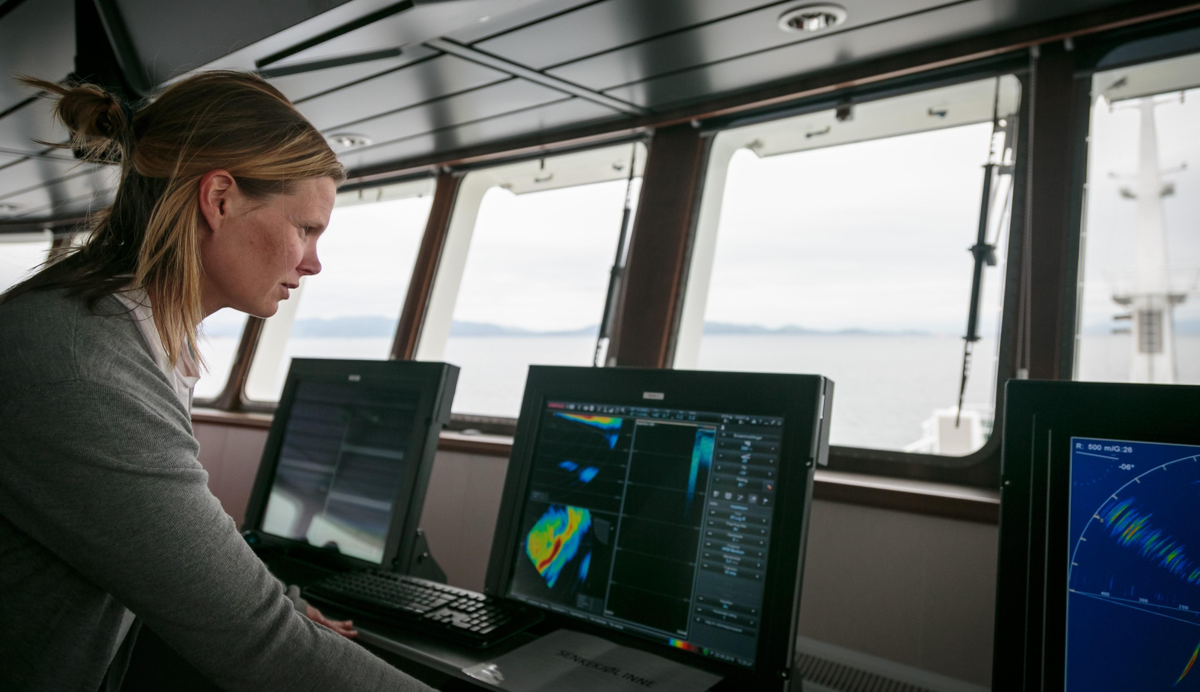 foto av forsker Maria Tenningen som står i styrhuset på et skip og ser på sonar-bildene.