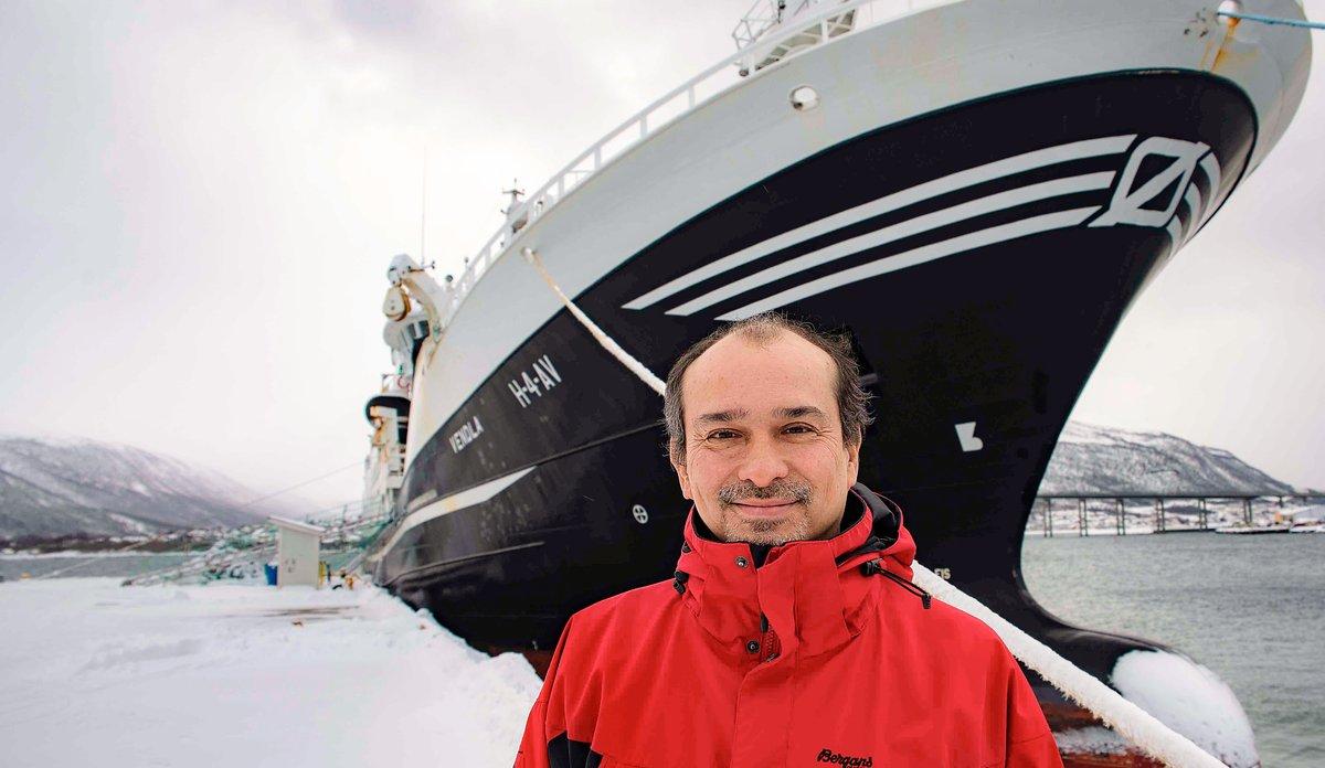 foto av en mann foran en fiskebåt